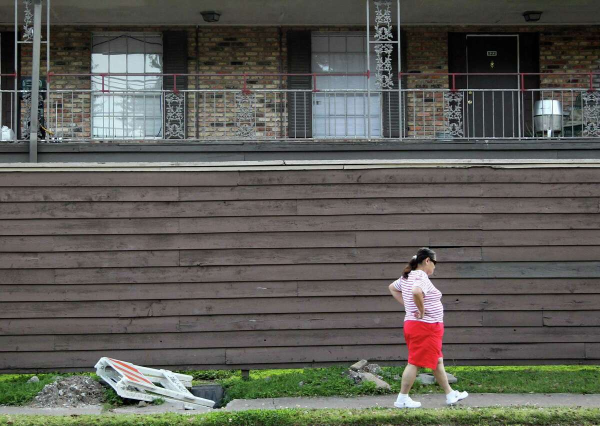 A woman walks the perimeter of Sharon Park Village Apartment complex in the southwest Houston on Saturday, April 13, 2013, in Houston. A proposed change to the city's development rules might spur the redevelopment of blighted properties. ( Mayra Beltran / Houston Chronicle )