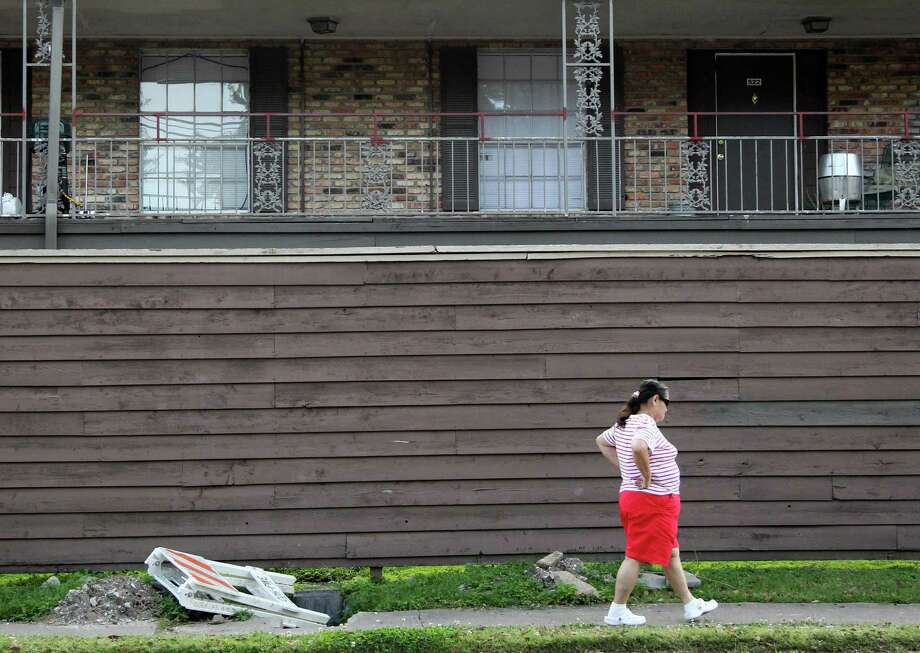 A woman walks the perimeter of Sharon Park Village Apartment complex in the southwest Houston on Saturday, April 13, 2013, in Houston. A proposed change to the city's development rules might spur the redevelopment of blighted properties. ( Mayra Beltran / Houston Chronicle ) Photo: Mayra Beltran, Staff / © 2013 Houston Chronicle