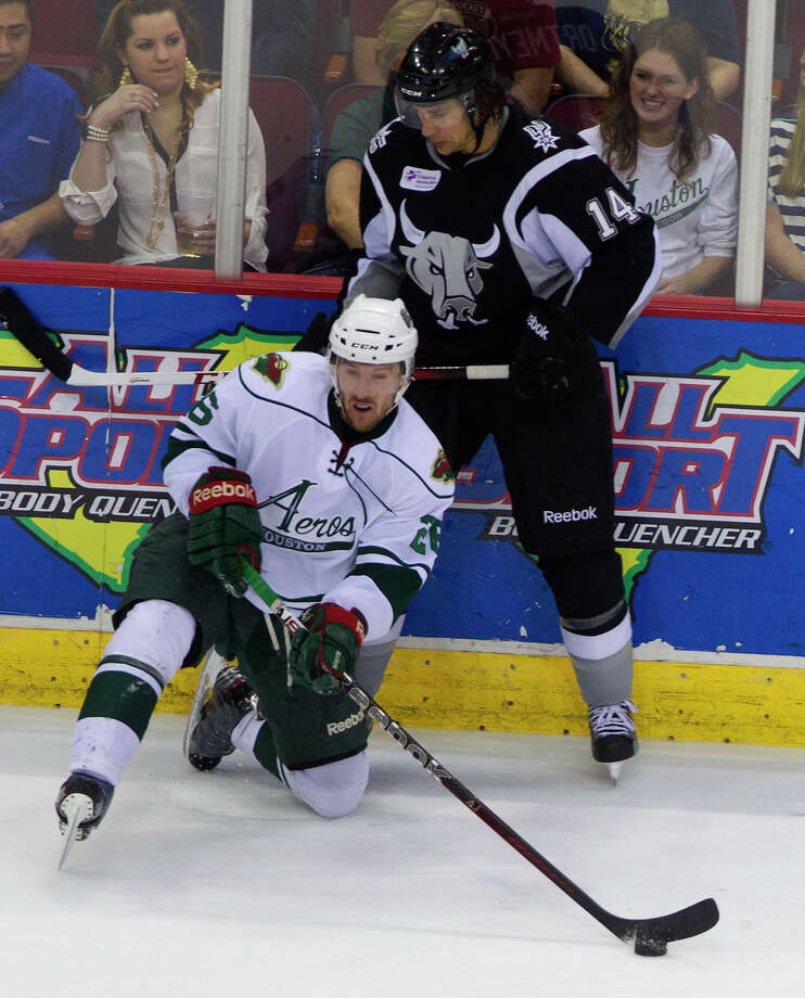 San Antonio Rampage right wing Jed Ortmeyer, left, looks on as Houston Aeros center David McIntyre, left, plays from a knee during the first period of the Aeros final regular-season game at the Toyota Center Saturday, April 13, 2013, in Houston. Photo: Cody Duty, Houston Chronicle / © 2013 Houston Chronicle
