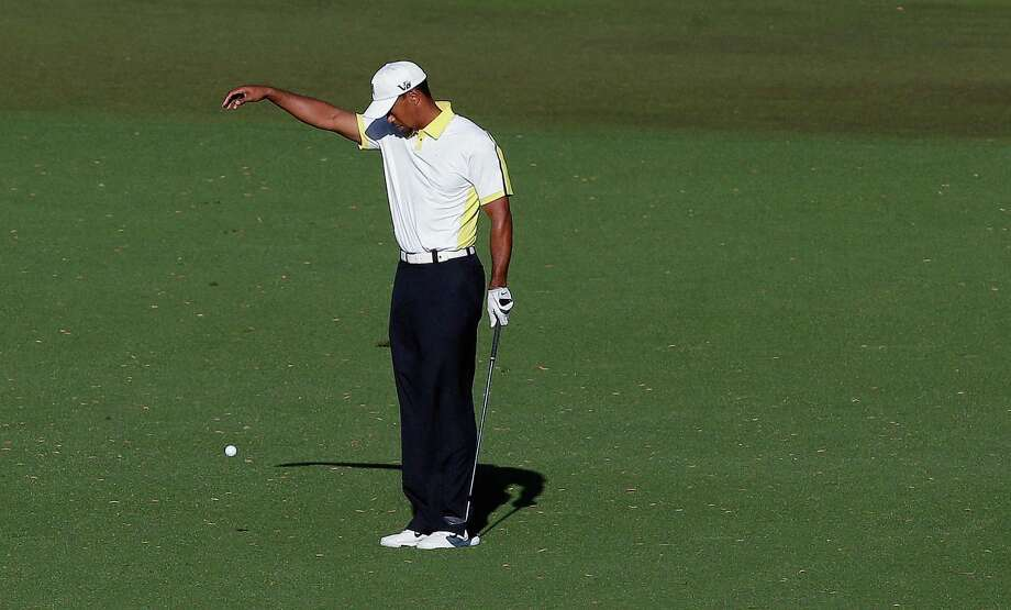 Tiger Woods takes a drop on the 15th hole after his ball went into the water during the second round of the Masters golf tournament Friday, April 12, 2013, in Augusta, Ga. The drop is being reviewed by the rules committee. (AP Photo/Charlie Riedel) Photo: Charlie Riedel