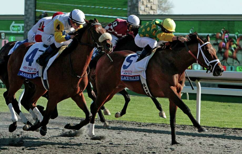 Java's War, front left, under jockey Julien Leparoux, runs down front-running Palace Malice, right, under jockey Garrett Gomez, in the final furlong to win the Blue Grass Stakes horse race at Keeneland Race Course in Lexington, Ky., Saturday, April 13, 2013. (AP Photo/Garry Jones) Photo: Garry Jones