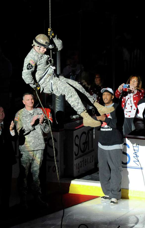 A member of the US Army repels to the floor to drop the first puck prior to the start of the Albany Devils' Binghamton Senators' hockey game in Albany, N.Y., Saturday, April 13, 2013. (Hans Pennink / Special to the Times Union) Photo: Hans Pennink / Hans Pennink