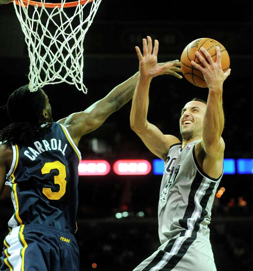 Manu Ginobili of the San Antonio Spurs scores as DeMarre Carroll of the Utah Jazz attempts the block during second-quarter NBA action at the AT&T Center on Saturday, Nov. 3, 2012. Photo: Billy Calzada, San Antonio Express-News / © 2012 San Antonio Express-News