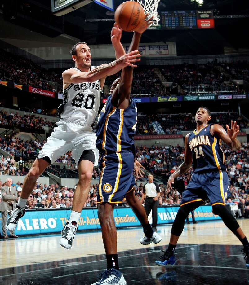 San Antonio Spurs' Manu Ginobili passes around Indiana Pacers' Ian Mahinmi as Indiana Pacers' Paul George looks on during second half action Monday Nov. 5, 2012 at the AT&T Center. The Spurs won 101-79. Photo: Edward A. Ornelas, San Antonio Express-News / © 2012 San Antonio Express-News