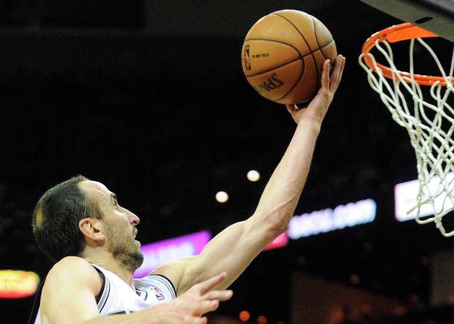 Manu Ginobili of the San Antonio Spurs scores two of his 23 points against the Houston Rockegts at the AT&T Center on Friday, Dec. 28, 2012. Photo: Billy Calzada, San Antonio Express-News / SAN ANTONIO EXPRESS-NEWS