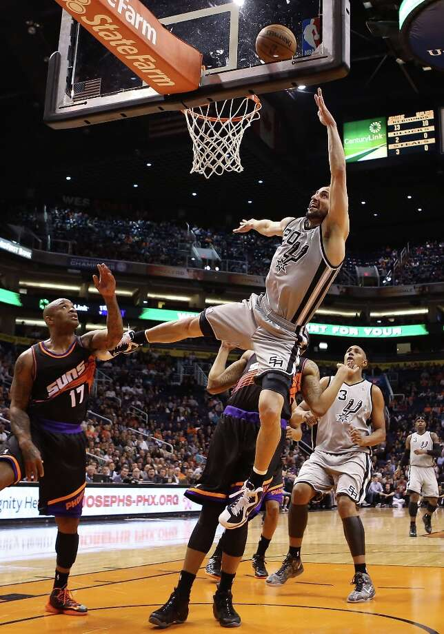 Manu Ginobili #20 of the San Antonio Spurs lays up a shot past P.J. Tucker #17 of the Phoenix Suns during the first half of the NBA game at US Airways Center on February 24, 2013 in Phoenix, Arizona. Photo: Christian Petersen, Getty Images / 2013 Getty Images