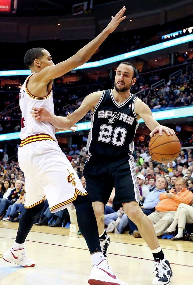 The Spurs' Manu Ginobili looks for room around Cleveland Cavaliers' Shaun Livingston during first half action Wednesday Feb. 13, 2013 at the Quicken Loans Arena in Cleveland, Ohio. Photo: Edward A. Ornelas, San Antonio Express-News / © 2013 San Antonio Express-News