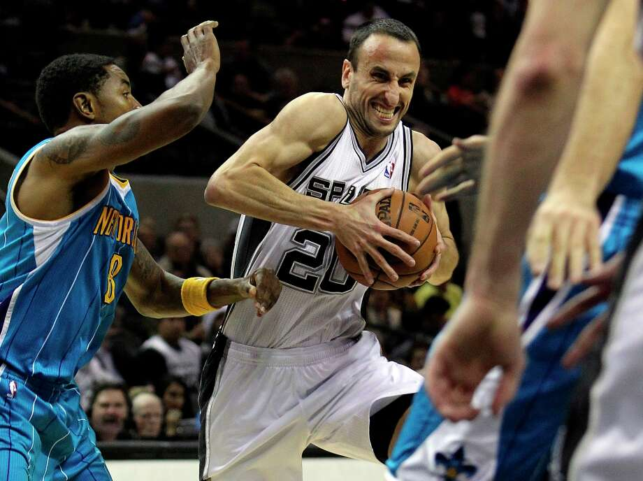 Spurs guard Manu Ginobili drives into the lane past Roger Mason, Jr. as San Antonio plays the New Orleans Hornets at the AT&T Center on December 21, 2012. Photo: Edward A. Ornelas, San Antonio Express-News / ©2012 San Antono Express-News
