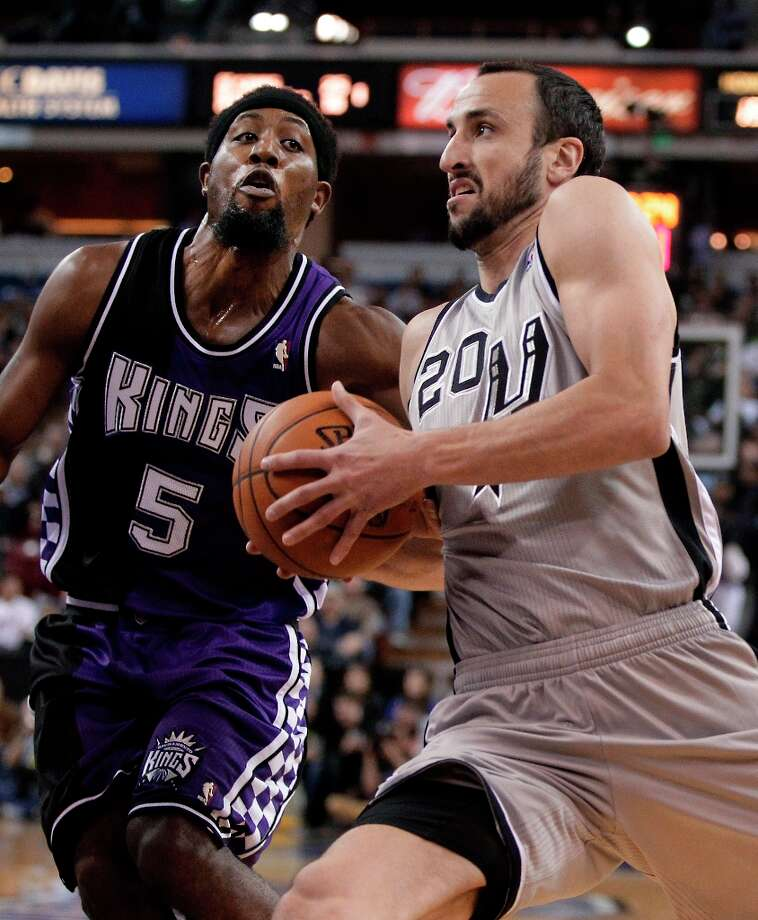 Spurs guard Manu Ginobili, right, drives against Sacramento Kings forward John Salmons during the first quarter in Sacramento, Calif., Tuesday, Feb. 19, 2013. Photo: Rich Pedroncelli, Associated Press / AP
