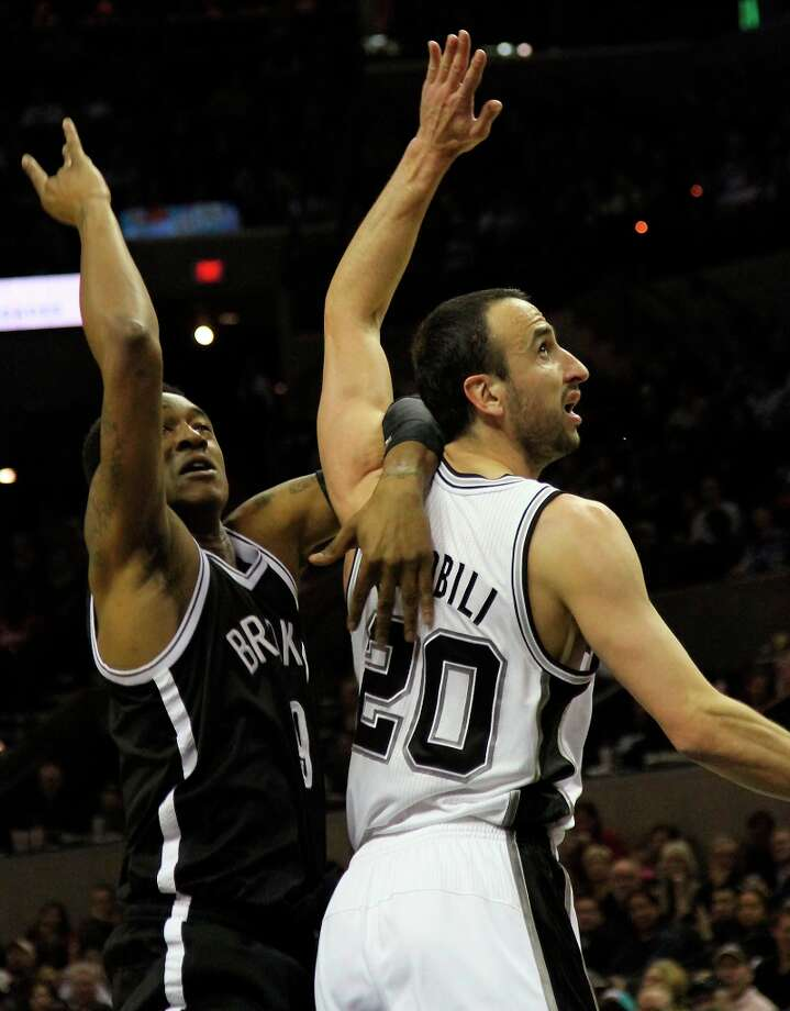 Spurs guard Manu Ginobili looks for a rebound against Brooklyn Nets Deron Williams in second half at the AT&T Center, Monday, Dec. 31, 2012. Photo: Bria M. Webb, San Antonio Express-News / @2012 San Antonio Express-News