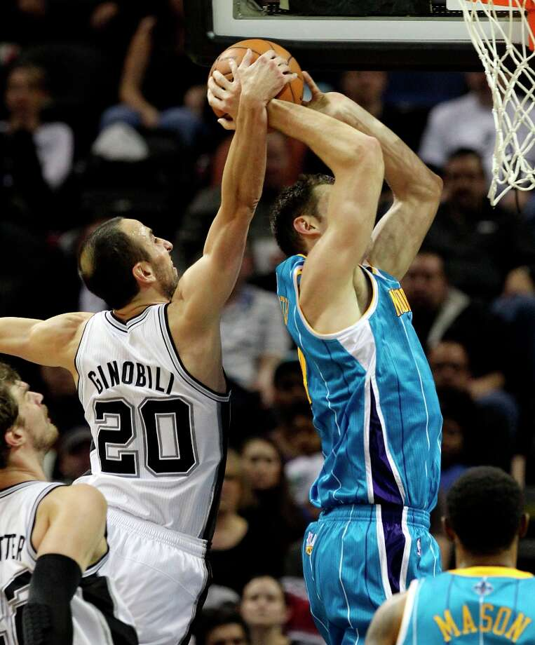 The Spurs' Manu Ginobili (20) makes a block against New Orleans Hornets' Jason Smith (14) in the second half on Wednesday, Jan. 23, 2013. Spurs defeated the Hornets, 106-102. Photo: Kin Man Hui, San Antonio Express-News / © 2012 San Antonio Express-News