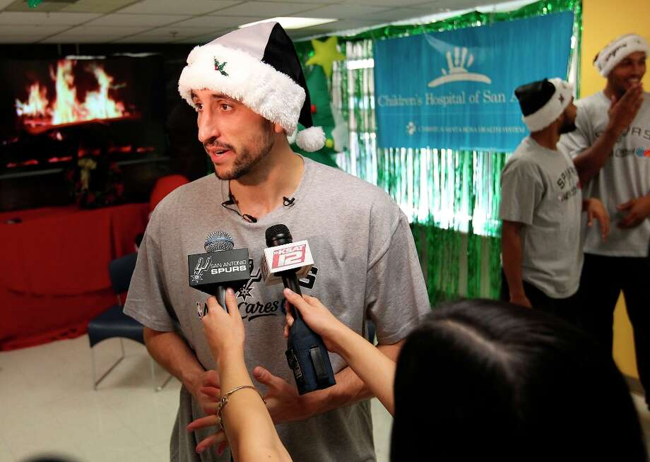 The Spurs' Manu Ginobili talks to the media after he and teammates Boris Diaw and Patty Mills took photos with young patients at the Children's Hospital of San Antonio on Tuesday, Dec. 4, 2012. As an annual affair, the Spurs players met with young hospitalized fans, signed mini-basketballs and posed for photos. A long line trailed into the hallway for a chance for those to meet with the players. Photo: Kin Man Hui, San Antonio Express-News / © 2012 San Antonio Express-News