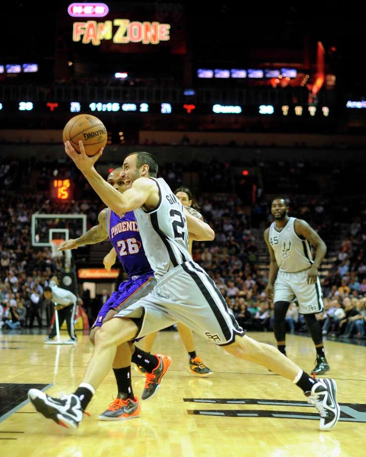 Manu Ginobili of the Spurs drives past Shannon Brown of the Phoenix Suns during first-half NBA action at the AT&T Center on Saturday, Jan. 26, 2013. Photo: Billy Calzada, San Antonio Express-News / SAN ANTONIO EXPRESS-NEWS