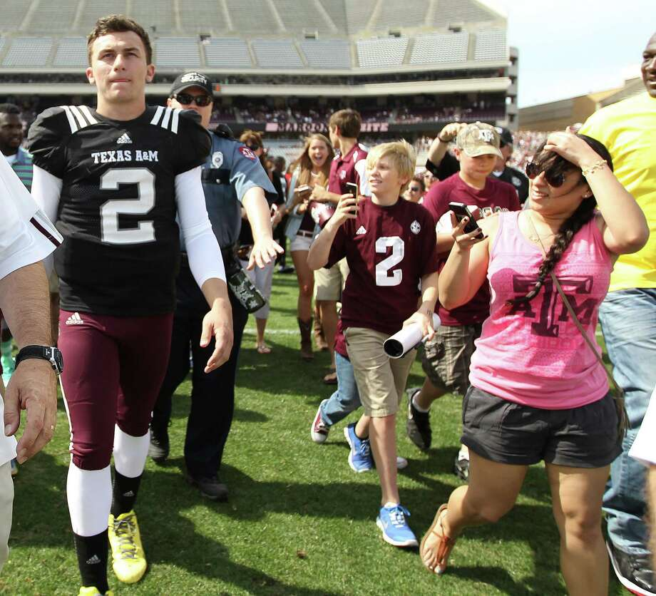 Texas A&M quarterback Johnny Manziel (2) is the center of attention as he leaves the field Saturday. Photo: Karen Warren, Staff / © 2013 Houston Chronicle