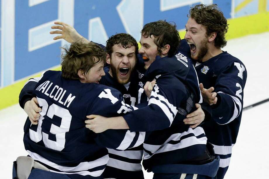 Yale goalie Jeff Malcolm (33) is swarmed by teammates after shutting out Quinnipiac 4-0 to win the NCAA men's college hockey Frozen Four national championship game in Pittsburgh, Saturday, April 13, 2013. Photo: Gene Puskar