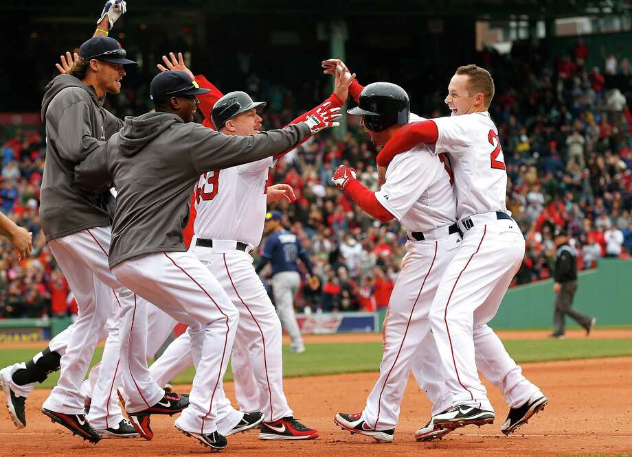 Shane Victorino, second from right, is mobbed by his Boston brethren after delivering a win for the Red Sox in the 10th inning on Saturday. Photo: Jim Rogash, Stringer / 2013 Getty Images