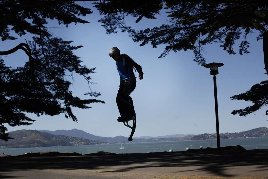 Wearing his jumping stilts, Rico Trias, 45, jumps on top of the hill at Fort Mason in San Francisco.