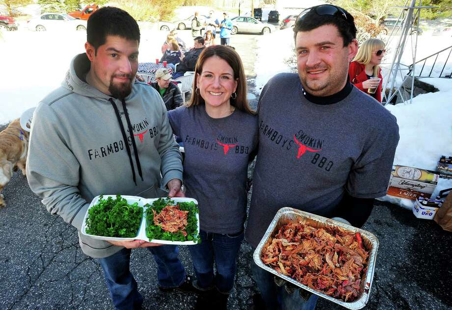 Chris Sparaco, left, helps Stacey and Matt Lombardo with their catering business, Farmboys Smokin' BBQ, during a cookout in Newtown, Conn. Saturday, March 10, 2013. They specialize in Southern-style, slow-cooked smoked barbecue, using a mobile smoker to cook on site. Homemade sauces are offered too, as well as several side dishes. Photo: Michael Duffy / The News-Times