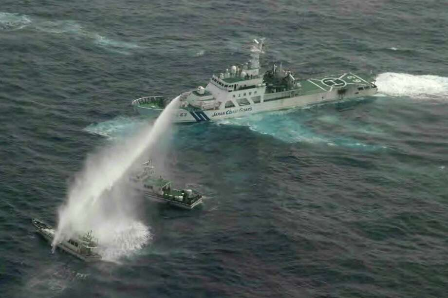 In this  Jan. 24, 2013 file photo released by Japan Coast Guard 11th Regional Headquarters, a Japan Coast Guard patrol boat uses water cannon to warn a Taiwan's leisure boat, left, and Taiwan Coast Guard boat off Uotsuri in Japanese and Diaoyu Dao in Chinese, the biggest island in the disputed Senkaku or Diaoyu islands in East China Sea. Four Taiwanese activists on the fishing boat attempted to sail to the disputed islands but were turned away by Japan Coast Guard. On Wednesday, April 10, 2013, Japan agreed to give Taiwanese fishing rights in waters near a group of Japanese-controlled islands in the East China Sea that are also claimed by China and Taiwan. (AP Photo/Japan Coast Guard 11th Regional Hardquarters) Photo: AP