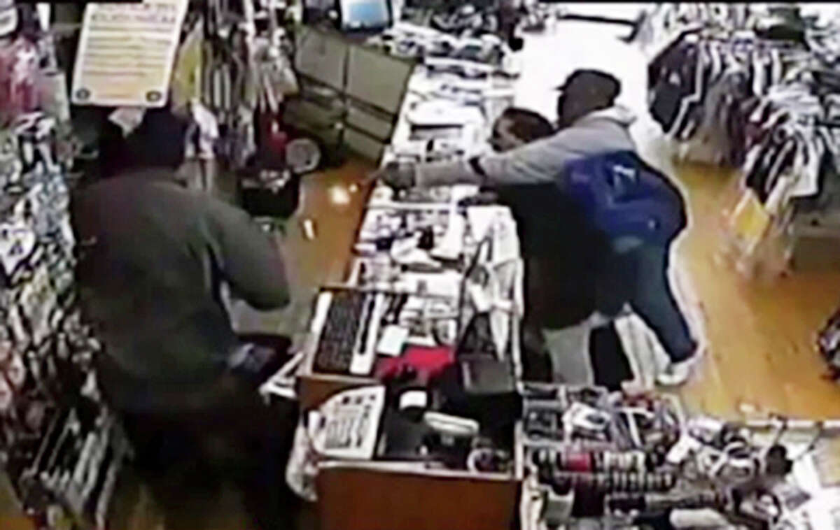 In this image taken from Tuesday, April 9, 2013 surveillance video provided courtesy of Quizhpe Gifts & Fashion, an armed robber, right, holding onto the shop owner Luis Quizhpe's brother-in-law, fires his gun at Quizhpe, obscured by a second robber at left, during a robbery attempt in Chicago's Logan Square neighborhood. The gunman fired multiple shots at Quizhpe, hitting him in the leg. But the wound failed to stop the shop owner's vigorous counterassault with a baseball bat against the pair of robbers. One man was charged with attempted murder and armed robbery and officers are searching for a second suspect in the incident.