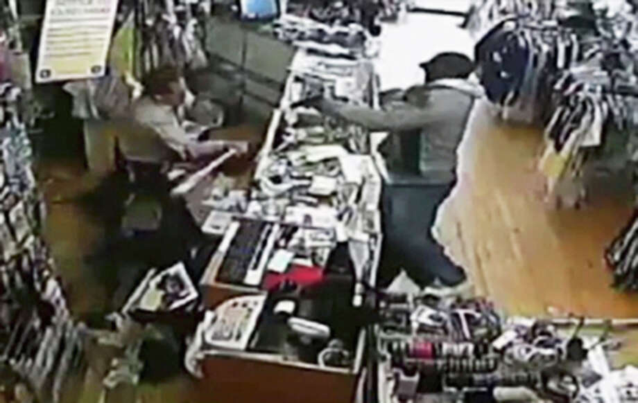In this image taken from Tuesday, April 9, 2013 surveillance video provided courtesy of Quizhpe Gifts & Fashion, shop owner Luis Quizhpe, left, uses a baseball bat to fight off an armed robber at his shop in Chicago's Logan Square neighborhood. The gunman fired multiple shots at Quizhpe, hitting him in the leg. But the wound failed to stop the shop owner's vigorous counterassault with a baseball bat against the pair of robbers. One man was charged with attempted murder and armed robbery and officers are searching for a second suspect in the incident. Photo: AP