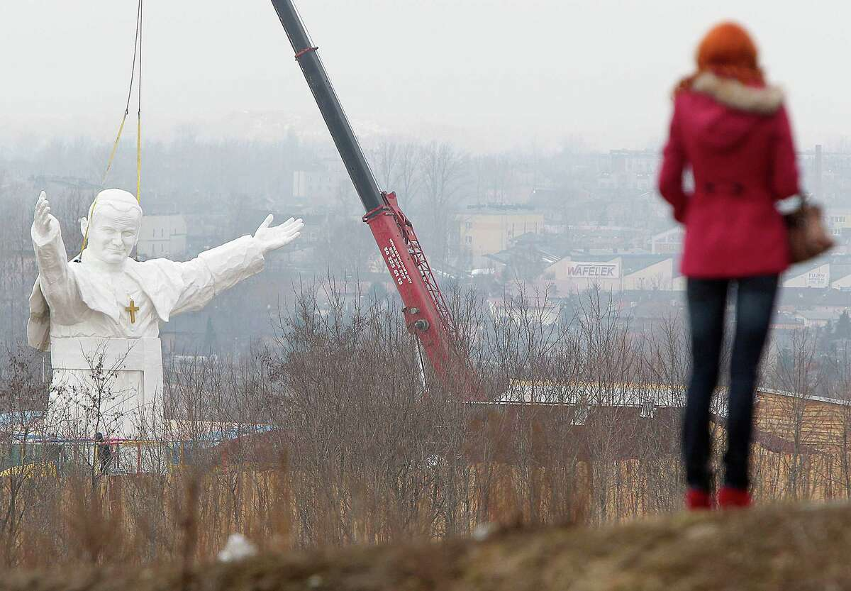 A woman looks at the giant statue of late Pope John Paul II being readied for unveiling this weekend, in Czestochowa, Poland, Tuesday, April 9, 2013. The 45.3-foot white fiberglass figure will tower over the southern city of Czestochowa, home to Poland's most important Catholic pilgrimage site, Jasna Gora. Funded by a private investor, the pontiff appears smiling and stretching his arms to the world.
