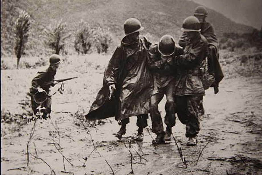 This image provided by the U.S. Army shows U.S. Army chaplain, Capt. Emil J. Kapaun, right, and Capt. Jerome A. Dolan, a medical officer with the 8th Cavalry regiment carrying an exhausted Soldier off a battlefield in Korea, Nov. 1950. President Barack Obama awarded the Medal of Honor Thursday April 11, 2013 to the Army chaplain from Kansas who risked his life dodging gunfire to provide medical and spiritual aid to wounded soldiers before dying in captivity more than 60 years ago during the Korean War. Photo: AP