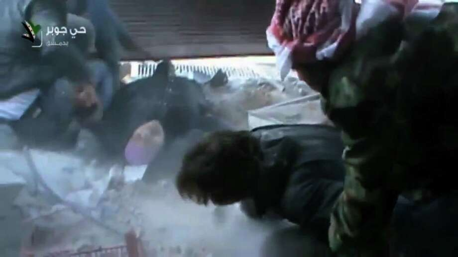 This image taken from video obtained from Shaam News Network, which has been authenticated based on its contents and other AP reporting, shows an injured Syrian woman rescued by rebels from a firefight in a street in the Jobar neighborhood in Damascus, Syria, Wednesday, April 10, 2013. Syrian President Bashar Assad's troops battled rebels in the outskirts of Damascus on Wednesday and pressed on with a counteroffensive against opposition fighters in the south to prevent their advance on the capital. Photo: AP