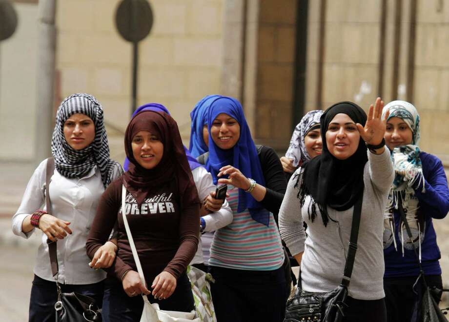 Egyptian girls walk past the Coptic cathedral in Cairo, Egypt, Monday, April 8, 2013. A senior Egyptian health ministry official says the death toll in clashes between Muslims and Christians in Cairo has risen to two. Dozens of people were injured. Photo: AP