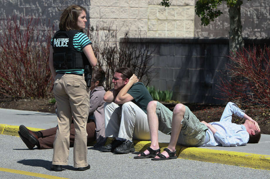 A police officer stands guard next to people on a curb outside the New River Valley Mall in Christiansburg, Va. on Friday, April 12, 2013. Officials say two women have been shot at the community college section of the mall and a suspect is in custody. Photo: AP
