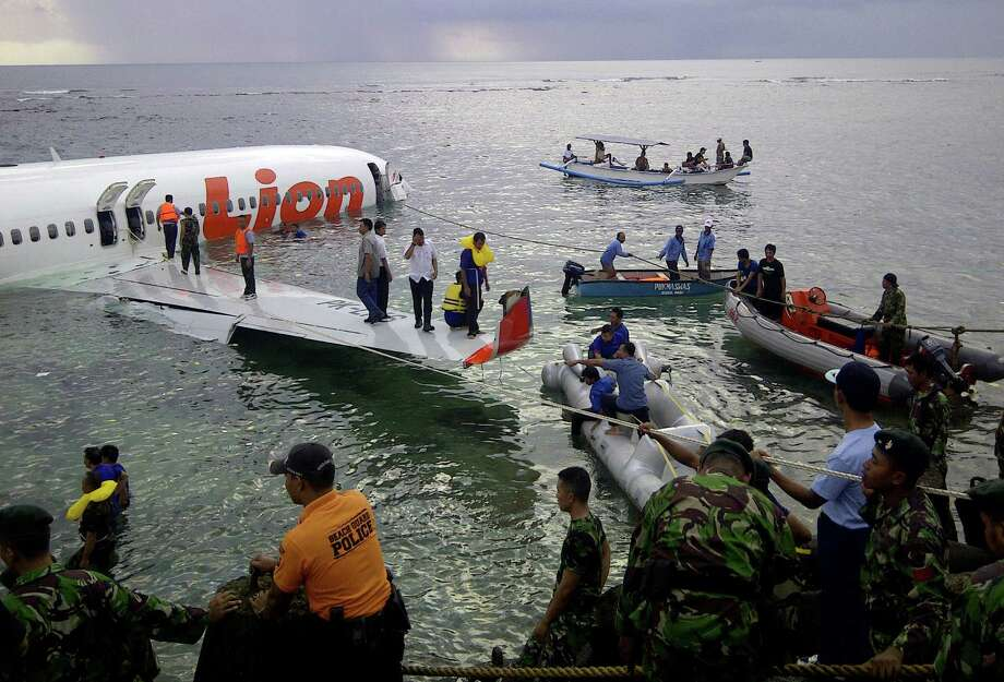 This photo released by Indonesia's National Rescue Team shows rescuers at the crash site of a Lion Air plane in Bali, Indonesia on Saturday, April 13, 2013. The plane carrying more than 100 passengers and crew overshot a runway on the Indonesian resort island of Bali on Saturday and crashed into the sea, injuring nearly two dozen people, officials said. Photo: AP