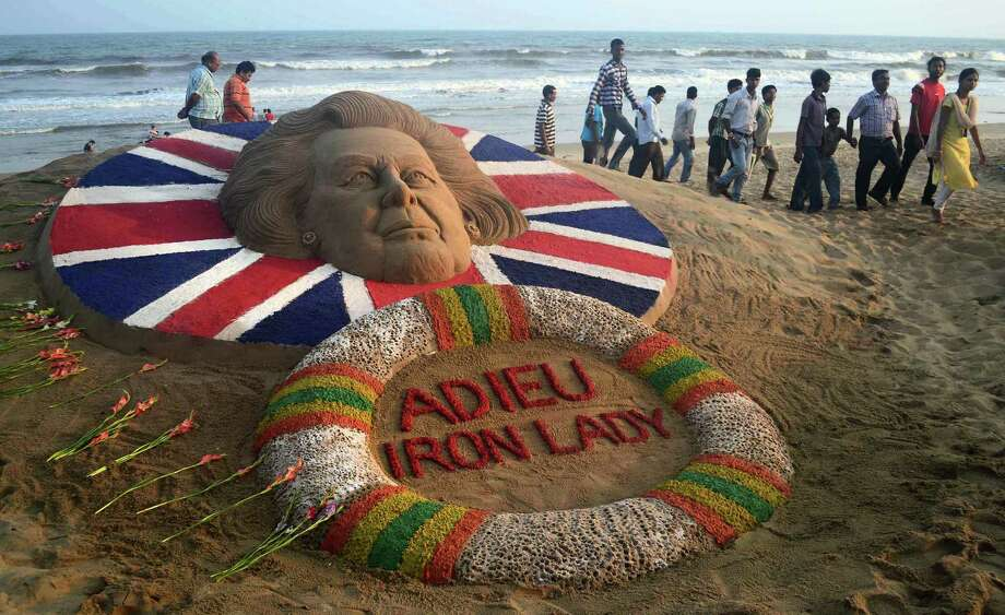 Indians look at the sand sculpture of former Britain's Prime Minister Margaret Thatcher, made by Sudarshan Pattnaik, at the golden beach of Puri, about 42 miles from the southeastern Indian temple city of Bhubaneswar, Tuesday, April 9, 2013. Photo: AP