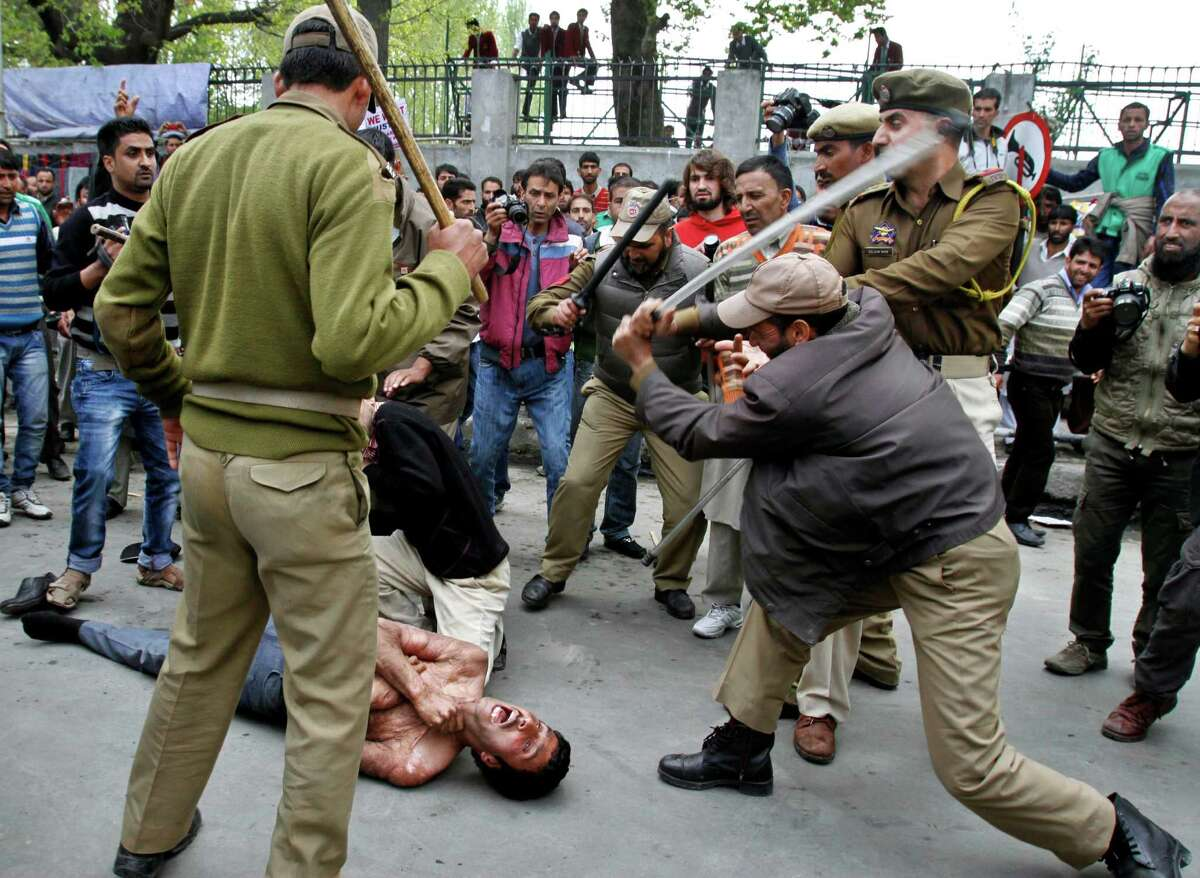 Indian policemen beat a Kashmiri government employee during a protest in Srinagar, India, Wednesday, April 10, 2013. Police used force to stop government employees during a protest called by the worker's union demanding regularization of contractual jobs and a hike in salary.