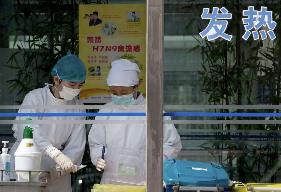 Nurses collect patients' blood samples at a specialized fever clinic inside the Ditan Hospital, where a Chinese girl is being treated for the H7N9 strain of bird flu, in Beijing Sunday, April 14, 2013. A World Health Organization official said Sunday that it wasn't surprising that a new strain of bird flu has spread to China's capital after sickening dozens in the eastern part of the country. Photo: AP