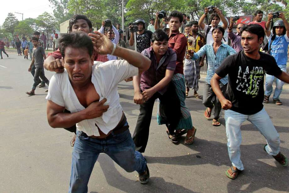 Bangladeshi activists of Hifazat-e-Islam beat a man who is alleged to have helped the police to identify the protesters during a strike in Dhaka, Bangladesh, Monday, April 8, 2013. At least 20 people were injured in southwestern Bangladesh as a hardline Islamic group enforces a general strike to back its demands for an anti-blasphemy law. Photo: AP
