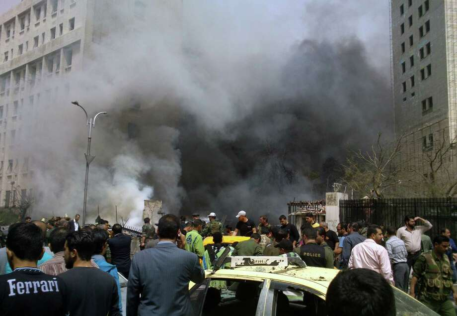 This photo released by the Syrian official news agency SANA, shows smoke rising from burned cars after a huge explosion shook the Sabaa Bahrat Square, one of the capital's biggest roundabouts, in Damascus, Syria, Monday, April. 8, 2013. A car bomb rocked a busy residential and commercial district in central Damascus on Monday, killing more than a dozen with many more injured and sending a huge cloud of black smoke billowing over the capital's skyline, Syrian state-run media said. Photo: AP