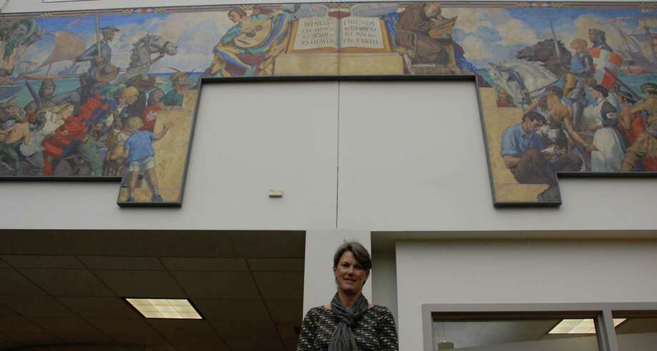 """Kathie Bennewitz stands beneath one of the Works Progress Administration murals created during the Depression -- this one, entitled """"Pageant of Literature"""" -- was done by Robert Lambdin in 1935 and is now on display at the Westport Public Library.  WESTPORT NEWS, CT 4/11/13 Photo: Jarret Liotta / Westport News contributed"""