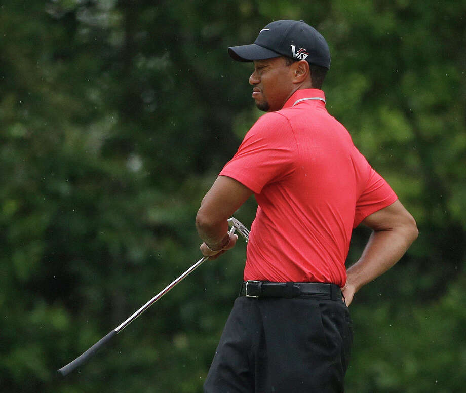 Tiger Woods stretches before putting on the fourth green during the fourth round of the Masters golf tournament Sunday, April 14, 2013, in Augusta, Ga. (AP Photo/Darron Cummings) Photo: Darron Cummings, Associated Press / AP