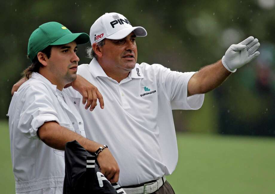 Angel Cabrera, of Argentina, discusses his next shot with his caddie son Angel Cabrera, Jr. on the second hole during the fourth round of the Masters golf tournament Sunday, April 14, 2013, in Augusta, Ga. (AP Photo/David J. Phillip) Photo: David J. Phillip, Associated Press / AP