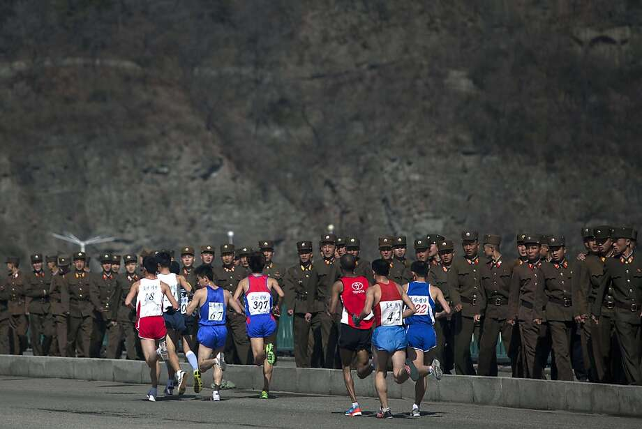 Marathon runners pass by a long row of North Korean soldiers as they cross a bridge in Pyongyang on Sunday, April 14, 2013. North Korea hosted the 26th Mangyongdae Prize Marathon to mark the upcoming April 15, 2013 birthday of the late leader Kim Il Sung. (AP Photo/David Guttenfelder) Photo: David Guttenfelder, Associated Press