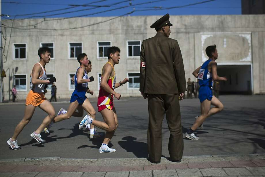 Marathon runners pass by a North Korean soldier during the race in Pyongyang on Sunday, April 14, 2013. North Korea hosted the 26th Mangyongdae Prize Marathon to mark the upcoming April 15, 2013 birthday of the late leader Kim Il Sung. (AP Photo/David Guttenfelder) Photo: David Guttenfelder, Associated Press