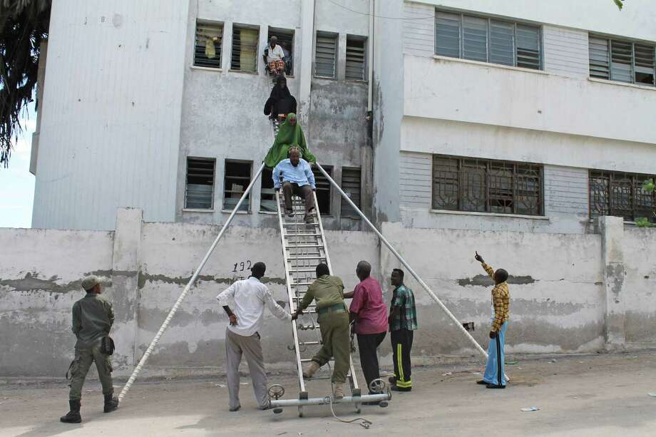 Survivors are helped to escape from a window at Mogadishu's court complex in Mogadishu, Somalia, Sunday, April 14, 2013. Militants launched a serious and sustained assault on Mogadishu's main court complex Sunday, detonating at least two blasts, taking an unknown number of hostages and exchanging extended volleys of gunfire with government security forces, witnesses said.(AP Photo/Farah Abdi Warsameh) Photo: Farah Abdi Warsameh