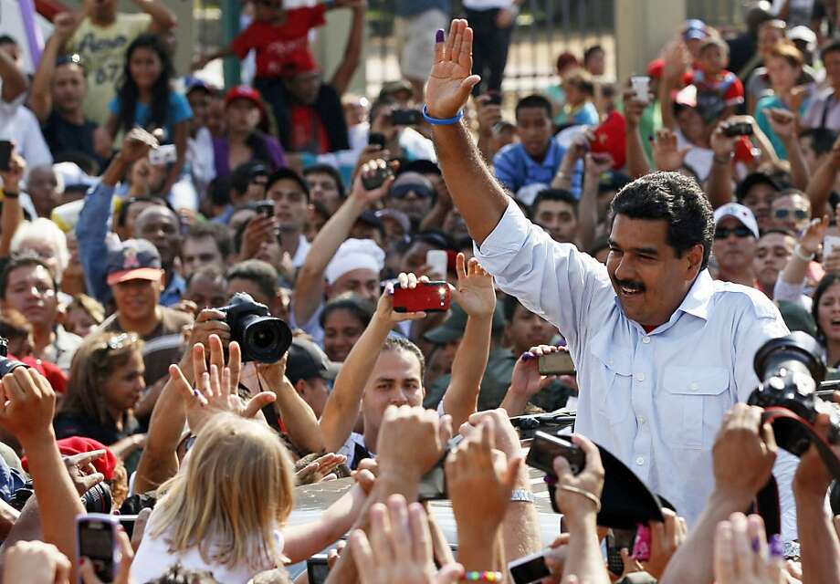 Venezuela's interim President Nicolas Maduro greets supporters as he leaves a polling station after voting in the presidential election in Caracas, Venezuela, Sunday, April 14, 2013.  Maduro, who served as late President Hugo Chavez's foreign minister and vice president, is running against opposition candidate Henrique Capriles. (AP Photo/Ariana Cubillos) Photo: Ariana Cubillos, Associated Press