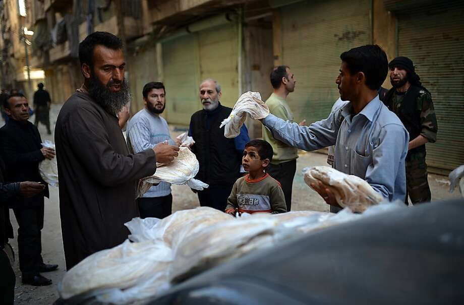 """TOPSHOTS Syrian men distribute bread in the Sheikh Maqsud neighbourhood of the northern city of Aleppo on April 14, 2013. Earlier in the week US President Barack Obama authorized the release of up to $10 million in food and medicine for rebels in Syria, saying the war there had reached a """"critical"""" point. AFP PHOTO / DIMITAR DILKOFFDIMITAR DILKOFF/AFP/Getty Images Photo: Dimitar Dilkoff, AFP/Getty Images"""