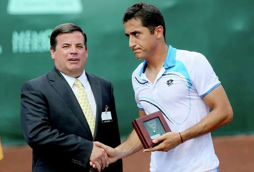 4/14/13:  Nicolas Almagro (ESP) is discouraged as he picks up his runner up trophy from River Oaks Country Club President Dan Moody after the finals of the River Oaks US Men's Clay Court Championship at River Oaks Country Club in Houston, Texas. Isner won 6-3, 7-5. Photo: Thomas B. Shea, For The Chronicle / © 2013 Thomas B. Shea