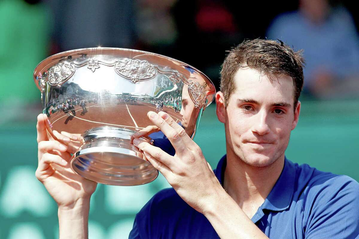 4/14/13: John Isner (USA) holds the trophy after defeating Nicolas Almagro (ESP) in the finals of the River Oaks US Men's Clay Court Championship at River Oaks Country Club in Houston, Texas. Isner won 6-3, 7-5.