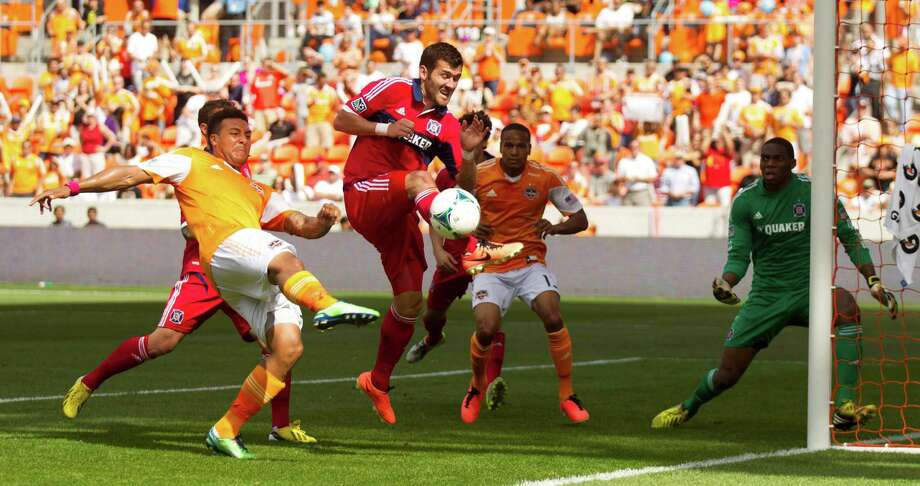 Houston Dynamo midfielder Giles Barnes, takes a shot with Chicago Fire defender Gonzalo Segares (13) defending during the first half of and MLS soccer game at BBVA Compass Stadium Sunday, April 14, 2013, in Houston. Photo: Brett Coomer, Houston Chronicle / © 2013 Houston Chronicle