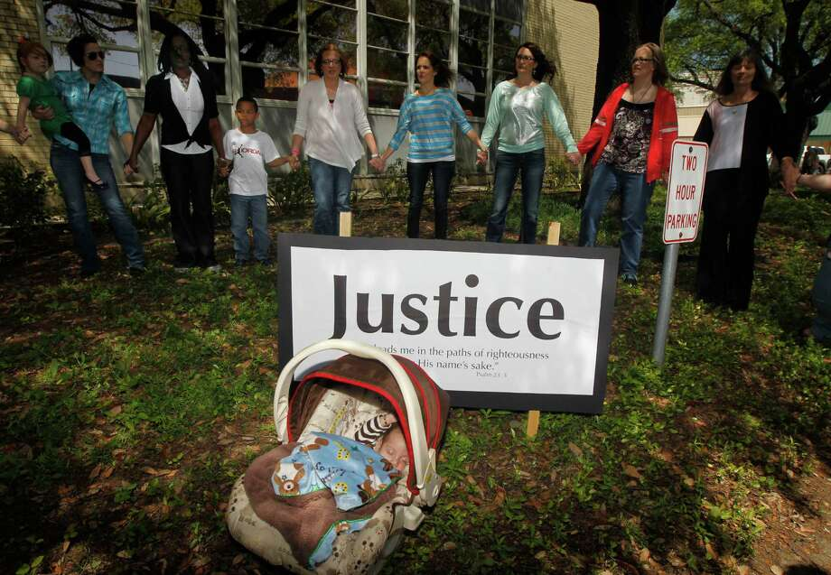 Angel Diaz, 3 months, daughter of Lorena Martinez, not pictured, rests as other pray during a prayer walk around the Kaufman County Courthouse in Kaufman, Texas on April 14, 2013. Authorities investigating the deaths of a North Texas district attorney and his wife appear to have narrowed their focus on a former justice of the peace prosecuted last year by the official for theft. (AP Photo/The Dallas Morning News, Michael Ainsworth) Photo: Michael Ainsworth, Associated Press / The Dallas Morning News