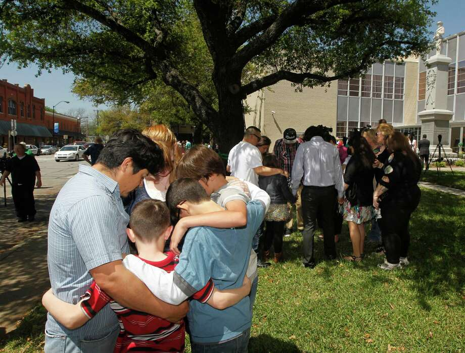 Families pray during a prayer walk around the Kaufman County Courthouse in Kaufman, Texas on Sunday, April 14, 2013. Authorities investigating the deaths of a North Texas district attorney and his wife appear to have narrowed their focus on a former justice of the peace prosecuted by the official for theft earlier this year. (AP Photo/The Dallas Morning News, Michael Ainsworth) Photo: Michael Ainsworth, Associated Press / The Dallas Morning News