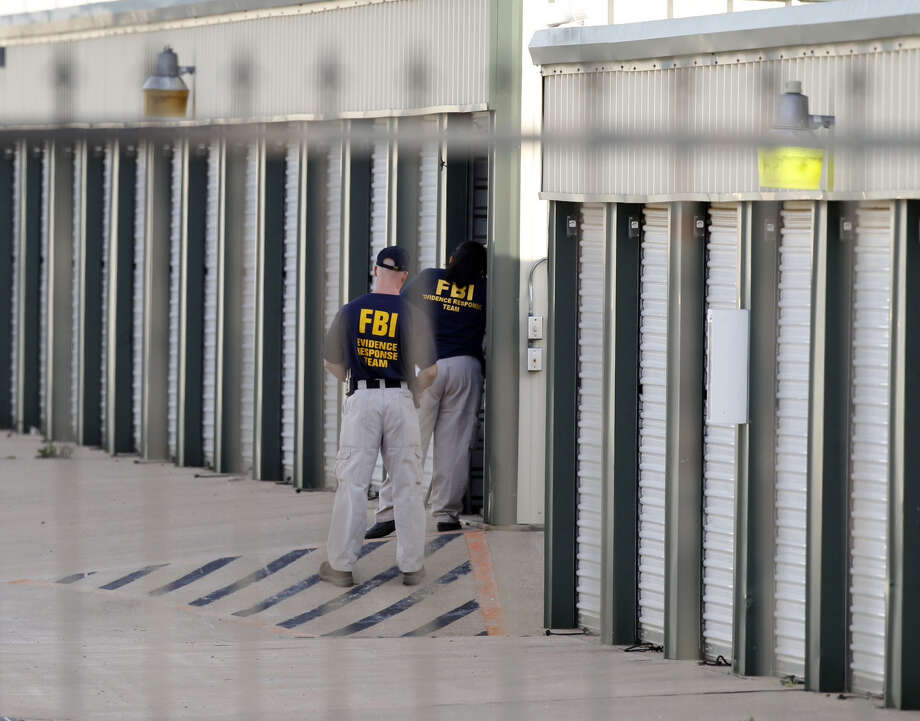 "Authorities search a storage unit at Gibson Self Storage as they continue to investigate the slayings of Kaufman County District Attorney Mike McLelland, his wife and a top prosecutor, Saturday, Aug. 13, 2013 in Seagoville, Texas. Authorities investigating the death of a Texas district attorney arrested Eric Williams, a former justice of the peace and charged him Saturday with making a ""terroristic threat"" after searching his home. (AP Photo/The Dallas Morning News, Michael Ainsworth)  MANDATORY CREDIT; MAGS OUT; TV OUT; INTERNET USE BY AP MEMBERS ONLY; NO SALES Photo: Michael Ainsworth, Associated Press / The Dallas Morning News"
